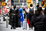 A person dressed in a Batman costume walks through Times Square displaying a Welcome Bank NYC message on monitors in New York on Wednesday, April 14, 2021. Photographer: Michael Nagle
