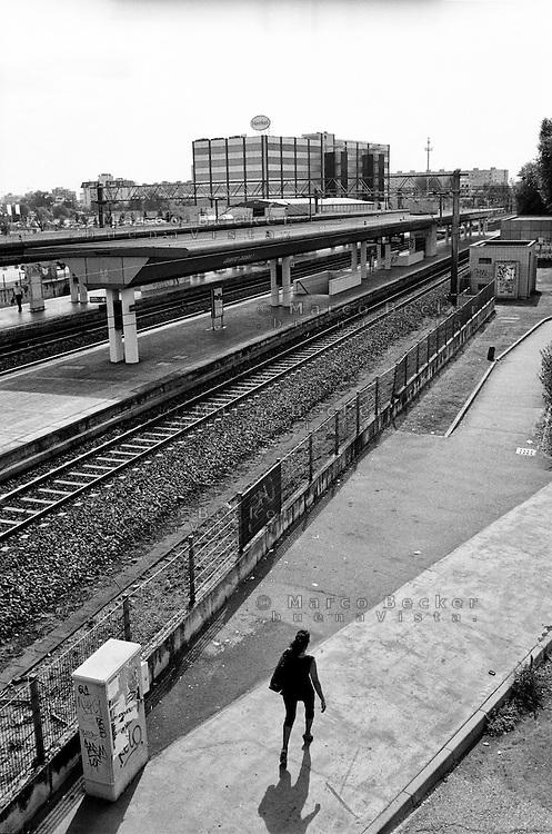 Milano, quartiere Quarto Oggiaro, periferia nord. Una persona e la stazione ferroviaria --- Milan, Quarto Oggiaro district, north periphery. A person and the railway station