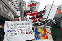 Moscow, Russia, 13/01/2013..A protester stands by a skip marked ?for garbage? that has been filled with portraits of Russian politicians. Thousands of opposition protesters carried posters of President Vladimir Putin and members of the Russian parliament with the word ?Shame? written in red at a protest called the March Against The Scoundrels. The protest was against the new law banning the adoption of Russian children by Americans, widely seen as a response to the recently passed USA Magnitsky Act.