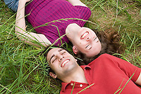Couple laying in grassy field<br />