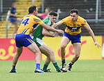 Paul White of Limerick in action against David Tubridy and Shane Brennan of Clare during their Munster championship quarter-final game in Cusack park. Photograph by John Kelly.
