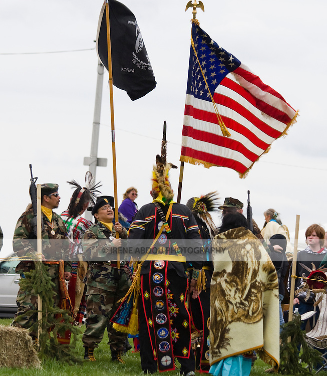 """Native Americans at the Healing Horse Spirit PowWow in Mt. Airy, Maryland carry an American flag POW-MIA flag.  They standy ready for the """"Grand Entrance.""""  Many Native Americans are U.S. soldiers or veterans.  One man in traditional regalia sports US military badges sewn down the length of his regalia in a vertical stripe."""