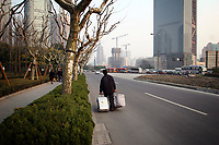 CHINA. Shanghai. A migrant worker walking through the modern Pudong area. Shanghai is a sprawling metropolis or 15 million people situated in south-east China. It is regarded as the country's showcase in development and modernity in modern China. This rapid development and modernization, never seen before on such a scale has however spawned countless environmental and social problems. 2008