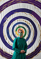"""BNPS.co.uk (01202) 558833<br /> Pic: ZacharyCulpin/BNPS<br /> <br /> 8 million stitches, 1 Holy Exhibition<br /> <br /> Pictured: Salisbury Cathedral's Verger, Kate Stubbings with an embroidery entitled, """"In the beginning…""""<br /> <br /> Twelve large embroidered panels fashioned from eight million stitches which tell the story of 'the Creation' have gone on display at Salisbury Cathedral.<br /> <br /> The panels, which measure up to 8ft by 11ft, are made from silk, hand-dyed materials, gold leaf and metallic leathers.<br /> <br /> They have been created by Devon-based textile artist Jacqui Parkinson who has dedicated three years to the solo project.<br /> <br /> The panels are inspired by the poetic verses of Genesis, the first book in the Bible, and include depictions of the Garden of Eden."""