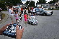 A police officer controls a remote control miniature police car with a full-size vehicle nearby at a community safety meeting in aneighborhood.