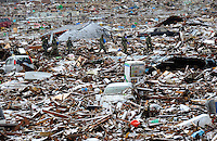 Japanese troops moved across a farmers field that has been littered with cars and splinters of houses, rooves of homes and even a drinks machine, all dumped there from the Natori village over a kilometer away, from the devastating Tsunami that followed the earthquake in Japan 11th March 2011.  The self defence force, police and other agencies were quick to move into the area looking for any possible survivors..16 Mar 2011.