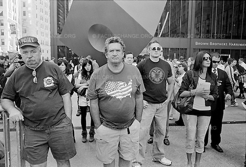 New York, New York.September 11, 2010..The ninth anniversary of the Sept. 11, 2001 terrorist attack on the World Trade Center, in Lower Manhattan. People watching the memorial ceremony on Broadway.