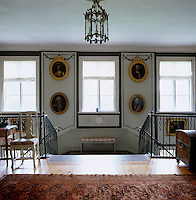 A bench stands on the landing of this double staircase which has gilt-framed portraits of ancestors on the walls