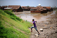 A boy runs past the submerged village of Besuki. Since May 2006, more than 10,000 people in the Porong subdistrict of Sidoarjo have been displaced by hot mud flowing from a natural gas well that was being drilled by the oil company Lapindo Brantas. The torrent of mud - up to 125,000 cubic metres per day - continued to flow three years later.
