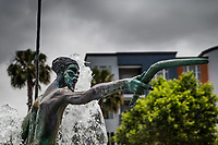 Close-up of the head of an Australian Aboriginal, his extended hand holding a booerang, part of a statue in a water fountain outside a medical office building in Fremont, California.