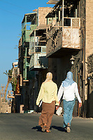 Two young women walking down the street wearing the traditional Islamic veil, Quoseir Village, Red Sea, Egypt.