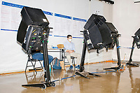 Poll workers sit near electronic voting machines in the School without Walls High School Ward 2 polling location in the Foggy Bottom area of Washington, D.C., on Election Day, Tue., Nov. 3, 2020. Poll workers said that the polling location was pretty quiet most of the day due to substantial mail-in voting done in DC.
