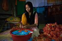 """Sumaiya* is 15 years old and lives with her parents, brother and sister in a slum in Dhaka, Bangladesh. She attends school but also works about 2 hours daily at home doing ornamental stitching, flower chains and dress decorations. Through this work she and her mother contribute to the family income. """"I started working when I was 11"""", tells Sumaiya*. """"The salary is not very good, but I can keep going to school and help my family with this extra income."""" Sumaiya* doing flower chains in their 1-bedroom house which the whole family shares."""