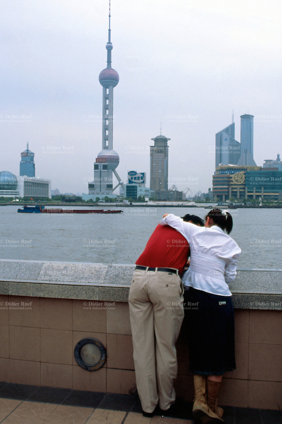 """China. Shanghai. Downtown. City center. Pudong skyline seen from """"The Bund"""". A couple shares tender and passionate moments near the river. Over 1 and 1/2 times larger than urban Shanghai itself, the Pudong new area consists of the entire eastern bank of the Huangpu river. Pudong is the new area of development where the growing business needs constantly new modern high buildings, real """"skyscrapers"""". Pudong has become Shanghai and China's economic powerhouse.The highest tower is the Oriental Pearl Tower wits 11 pink baubles.The Bund is the most impressive 2 km in Shanghai.  © 2002 Didier Ruef"""