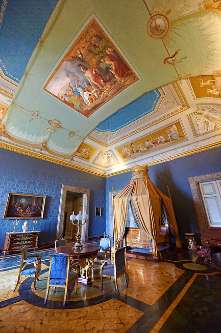"""""""The Bedroom of Francis II"""". The room furnished with a four poster bed, chest of drawers and table in the Empire Style in mahogany & gilt. The vaulted ceiling is freaked with an allegory of the victory of Napoleon over the Bourbons: the Glory of Thesus slaying the Minataur, by Giuseppe Cammarano  .  The Bourbon Kings of Naples Royal Palace of Caserta, Italy."""