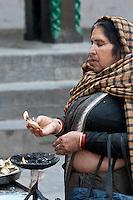 Nepal, Kathmandu.  Hindu Woman Praying while Holding a Candle Offering to Hanuman Statue, Durbar Square.