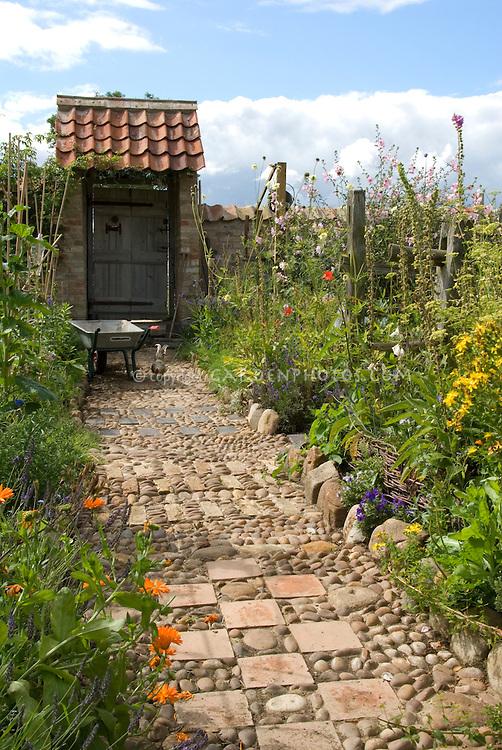Garden path of stones, pebbles & tiles leading to garden gate door, with wheelbarrow, chicken, vegetable and flower garden borders, blue sky and clouds, wide view . Board and batten door