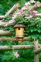 Lathe turned handmade birdhouse on garden arbor with clematis vines and pink flowers, midwest USA