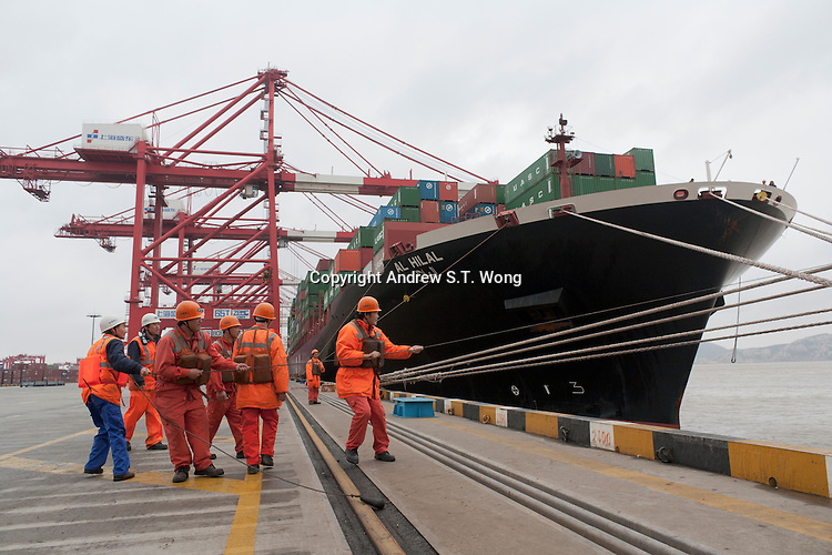 Chinese workers help a container ship dock at Yangshan Deep Water Container Port in Shanghai, China on November 10, 2009.