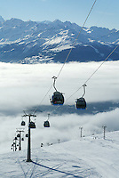 """Switzerland. Valais. Crans Montana. Winter ski resort. CMA ( Crans Montana Aminona) blue cable cars and ski lifts are carrying people to the top of the mountain, while other are skiing down  the """"Pas du loup"""" slopes on a sunny day with blue sky. The fog is covering the Rhone valley. © 2005 Didier Ruef"""