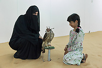 "United Arab Emirates (UAE). Abu Dhabi. Ayesha Matar Al Mansoori, her daughter Osha and a falcon on stool inside an air conditioned room at Abu Dhabi Falconers Club. Ayesha Al Mansoori is the first woman falconer in the UAE and the only member of the Ladies Falconer Club. She wears a black abaya and a niqab. The abaya, sometimes also called an aba, is a simple, loose over-garment, essentially a robe-like dress, worn by some women in parts of the Muslim world and the Arabian Peninsula. The abaya covers the whole body except the head, feet, and hands. It can be worn with the niqāb, a face veil covering all but the eyes.The muslim women who wear the niqab do so in places where they may encounter non-mahram (non-related) men. Falcons are birds of prey in the genus Falco, which includes about 40 species. Adult falcons have thin, tapered wings, which enable them to fly at high speed and change direction rapidly. Additionally, they have keen eyesight for detecting food at a distance or during flight, strong feet equipped with talons for grasping or killing prey, and powerful, curved beaks for tearing flesh. Falcons kill with their beaks, using a ""tooth"" on the side of their beaks. The United Arab Emirates (UAE) is a country in Western Asia at the northeast end of the Arabian Peninsula. 20.02.2020  © 2020 Didier Ruef"