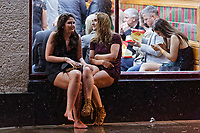 Pictured: Two young women, one of whom is barefoot, rest on the window ledge of a takeaway. Sunday 31 December 2017 and 01 January 2018<br /> Re: New Year revellers in Wind Street, Swansea, Wales, UK
