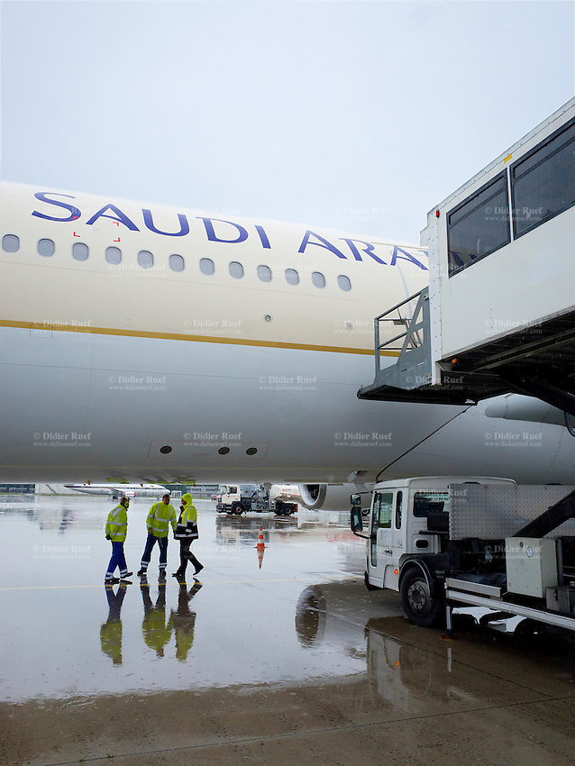 """Germany. Bavaria state. Munich Airport. Ramp agents standing on a rainy day under a Saudi Arabian Airbus A340. Ramp agents are also known as baggage handlers and loaders or as aircraft load agents. A common airline slang term for a ramp agent is """"ramper"""" or """"below the wing employee"""" to denote the ramp agent's particular on-the-ground work environment. The airport apron is the area of an airport where aircraft are parked, unloaded or loaded, refueled, or boarded. All vehicles, aircraft and people using the apron are referred to as apron traffic.The airport is located 28.5 km northeast of Munich near the old city of Freising and is named in memory of the former Bavarian Prime minister Franz Josef Strauss. Munich is the capital and largest city of the German state of Bavaria. 13.08.2014 © 2014 Didier Ruef"""