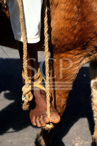 Bahia, Brazil. Muleteer (mule rider) foot on a stirrup made of a knot in a piece of rope.