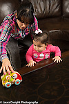 12 month old baby girl shown how new toy works by mother