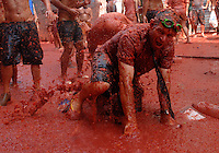 BUNYOL, SPAIN - AUGUST 31: A person immersed in tomato juice during the tomato battle 'Tomatina' August 31, 2005 in Bunyol, Valencia, Spain. Approximately 45,000 people pelted each other with a little over 100.000 kilograms of tomatoes. The tomatina is known as the world's largest tomato battle. Photo by Ander Gillenea