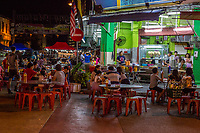 Families Dining Outdoors at Night at a Sidewalk Cafe, Ipoh, Malaysia.