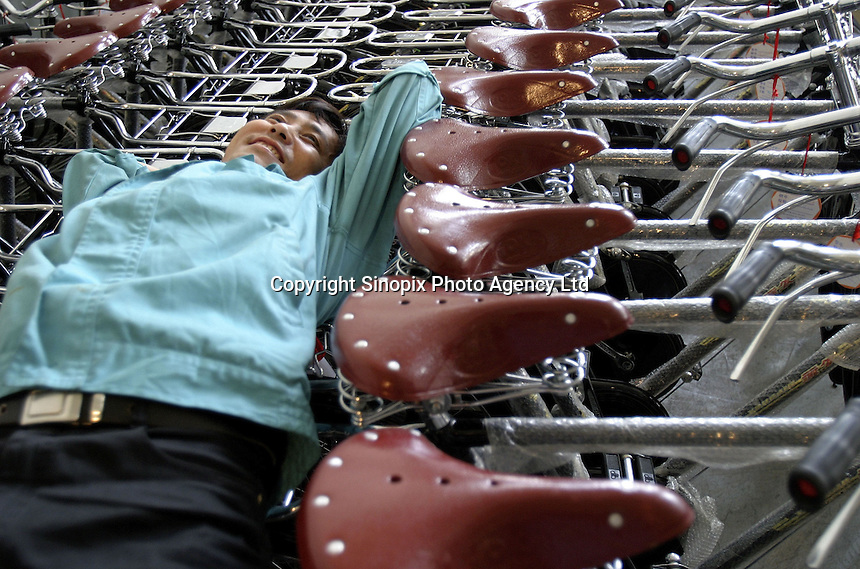 A worker takes an after-lunch siesta laying on top of tightly packed bicycles at the Shanghai Forever Bicycle Factory (SFBF) in Shanghai, China. ©Qilai Shen/Sinopix