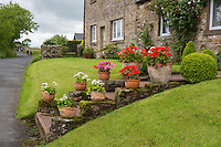Banks, Cumbria, England, UK.  Village House on the Route of Hadrian's Wall Footpath.  Hikers in the Distance.