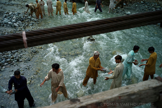 Men standing in a river pass rocks to repair where the road collapsed due to severe flooding in New Chail, in the Swat valley, Pakistan, on Aug. 22, 2010. Pakistan suffered the worst flooding in its history.