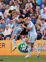 Long Tan (27) of  D.C. United goes up for a header with Michael Harrington (2) and Aurelien Collin (78) of Sporting Kansas City during the game at Livestrong Sporting Park in Kansas City, Kansas.  D.C. United lost to Sporting Kansas City, 1-0.