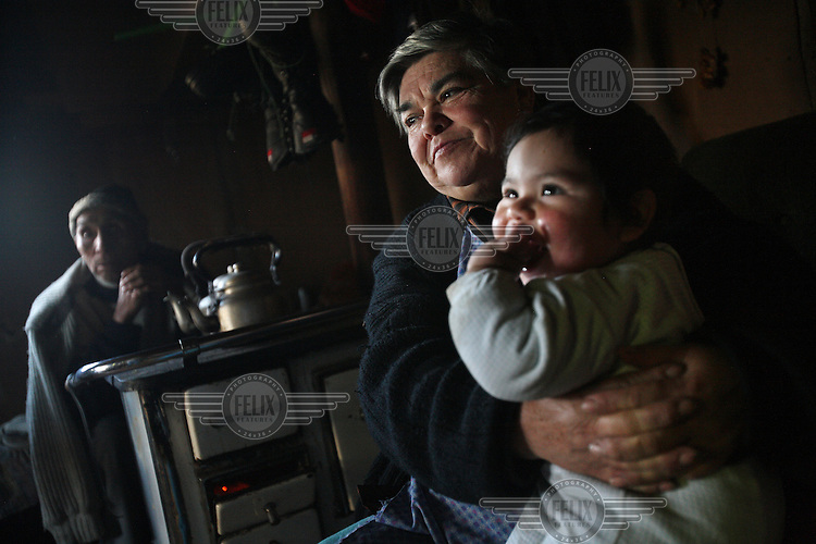 A family sits around a stove on the island of Teuquelin. This lies off the coast of a larger island called Chiloe that is itself off southern Chile. The only inhabitants of Teuquelin are the Peranchiguay family whose descendants arrived there two hundred years ago. Now only a few elderly people, women and children live there. The men and youth have all left in search of work. Those left behind make a living by harvesting Luga, an algae that is used in the production of shampoo and nappies.
