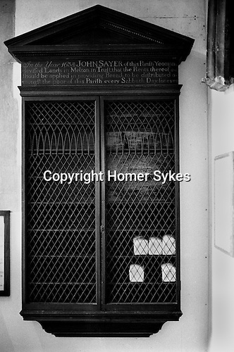 """John Sayer Charity, Woodbridge Suffolk. England 1975. Loafs of bread left for the poor in the Bread Cupboard in porch of St Marys Church.<br /> <br /> Written on the  Bread Cupboard, """"In the Year 1638; JOHN SAYER of this Parish Yeoman, devifed Lands in Melton, in Trust, that the Rents thereof and should be applied in providing Bread; to be distributed amongst the poor of this Parish every Sabbath Day for ever."""""""