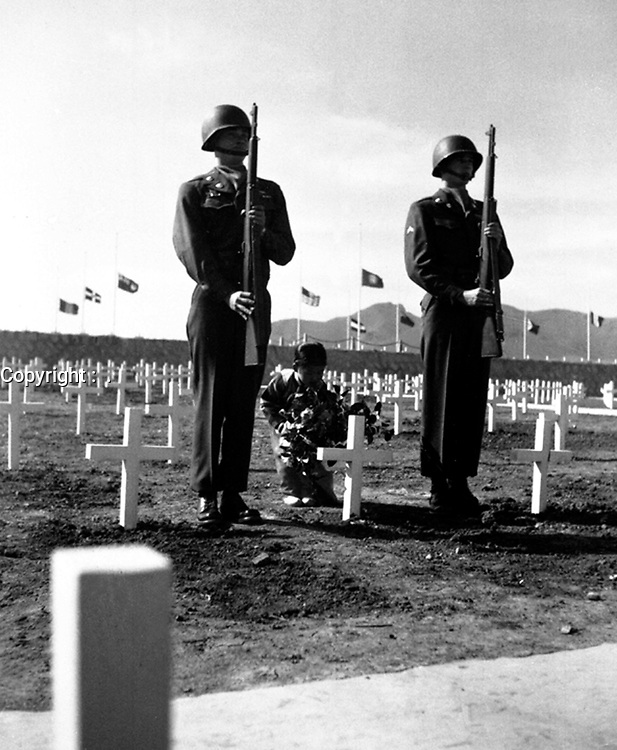A little Korean girl places a wreath of flowers on the grave of an American soldier, while Pfc. Chester Painter and Cpl. Harry May present arms, at the United Nations cemetery in Pusan.  April 9, 1951.  Cpl. Alex Klein. (Army)<br /> NARA FILE #:  111-C-6425<br /> WAR & CONFLICT BOOK #:  1522