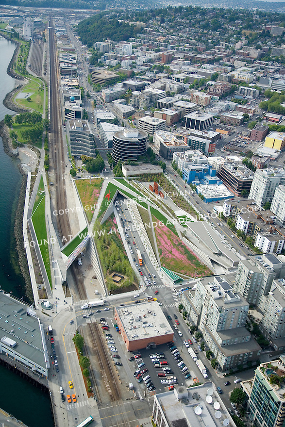 Aerial view looking north along the Seattle waterfront at the Olympic Sculpture Park.  Elliott Bay is to the left and Elliott Avenue, a major thoroughfare, runs underneath the center of the park.  The BNSF railroad train tracks that supply the Port of Seattle were another major obstacle to work around.  More than 200,000 yards of fill were added to raise the site of the park above the existing thoroughfares.