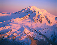 Aerial - sunset lighting on NW aspect of Mount Baker, North Cascades Mountain Range, Washington State