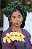 Myanmar, Burma.  Burmese Woman Offering Bananas for Sale, near Bagan.