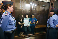 17/08/2012, Moscow, Russia..Inside the courtroom's glass cage Maria Alyokhina holds the trial verdict while Nadezhda Tolokonnikova waves her handcuffs, as they and Yekaterina Samutsevich of punk band Pussy Riot are sentenced to two years in prison for their performance in the Christ The Saviour Cathedral.