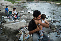 "November 07, 2014. ""Water it´s the real thing""<br /> Edwin Salguero with his son Edwin in Acelhuate river (Nejapa, El Salvador). He does' t have drinking water at home. The river is contaminated. Edwin and his family have to walk near two hours to get the river. <br /> The people of Nejapa in El Salvador, have no drinking water because the Coca -Cola company overexploited the aquifer in the area, the most important source of water in this Central American country. This means that the population has to walk for hours to get water from wells and rivers. The problem is that these rivers and wells are contaminated by discharges that makes Coca- Cola and other factories that are installed in the area. The problem can increase: Coca Cola company has expansion plans, something that communities and NGOs want to stop. To make a liter of Coca Cola are needed 2,4 liters of water. ©Calamar2/ Pedro ARMESTRE"