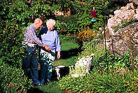 Senior couple touring and admiring their flower garden.