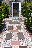 Entrance to house made more appealing with simple flagstone and pebble path and tier of plants and shrubs allee. Think Viburnum shrubs