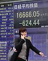 Pedestrians walk past a share prices board in Tokyo