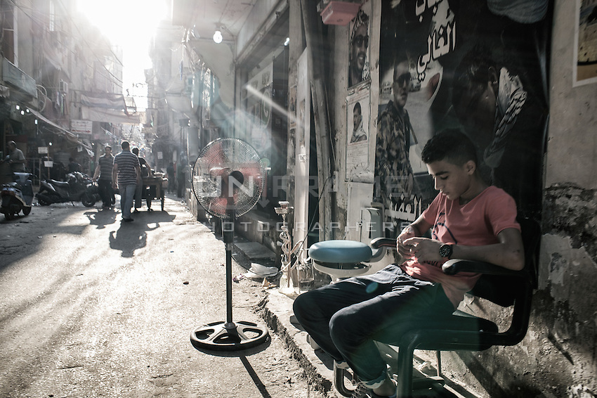 Teenager at the market street of Sabra, outside the Shatila camp playing with his phone wfil waiting for custmers. Beirut. Lebanon, August 2015