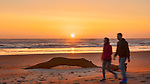 Couple walks the beach at Cape Disappointment State Park, Washington, at sunset.