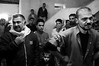 Baghdad, Iraq, March 28, 2003.Stunned men inside Moussa Khadoum mosq mourn 52 victims of the unidentified missile that exploded at dusk in the middle of a crowded market in Al Shuala', a very poor area of North West Baghdad.