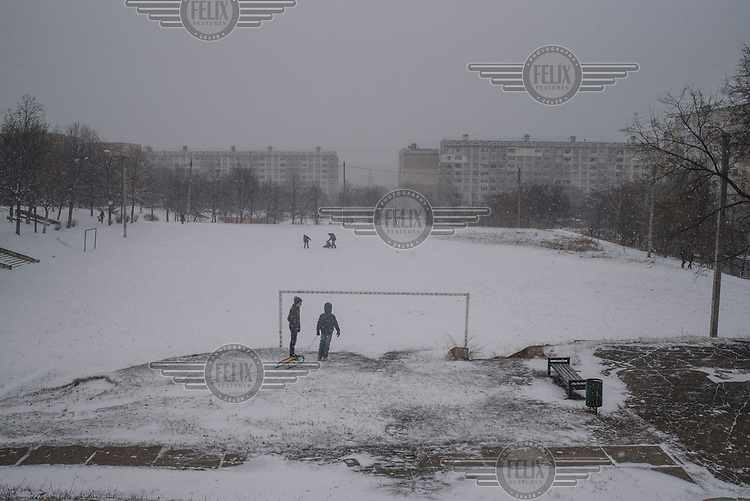 Children play with their sledges on a snow covered a football pitch in the Ciocana district.